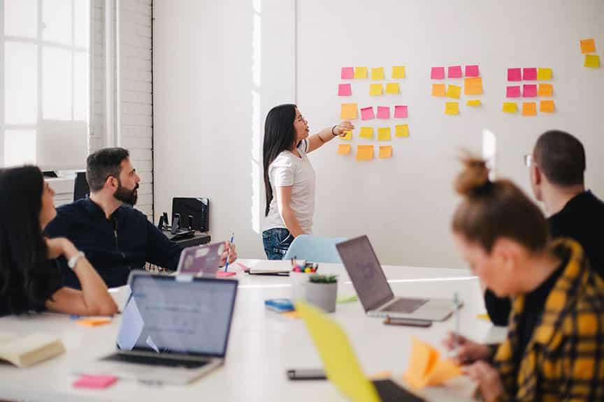 Photo d'une réunion avec des post-it colorés sur un mur
