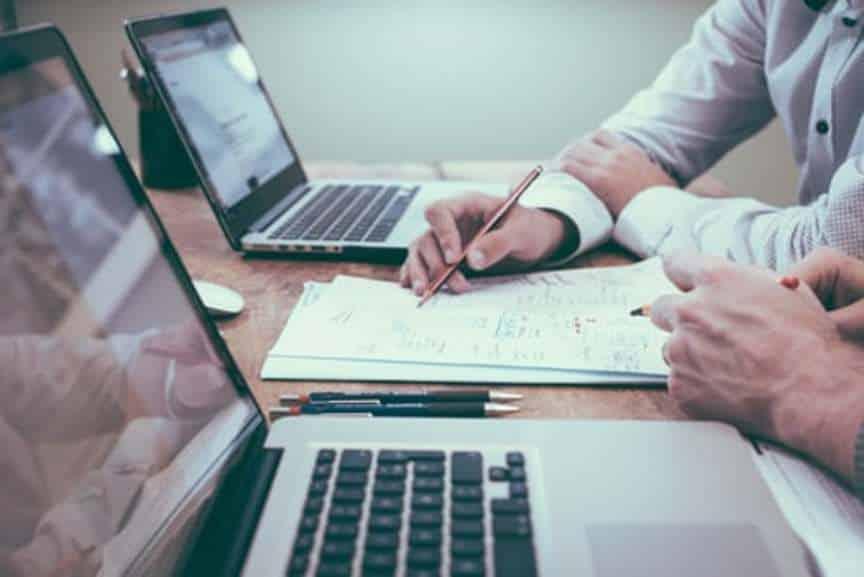 2 ordinateurs portables sur table et 2 collègues au travail